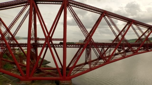 stunning aerial shot of the forth rail bridge during the day in south queensferry with a steam train passing by - scotland stock videos & royalty-free footage