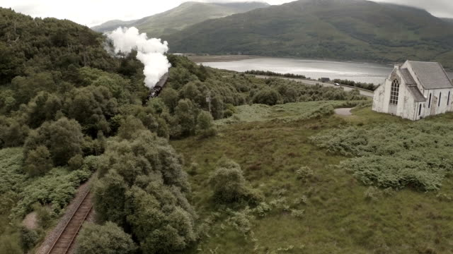 stunning aerial shot of the jacobite steam train passing a small church set among stunning scenary in the scottish highlands - steam train stock videos & royalty-free footage
