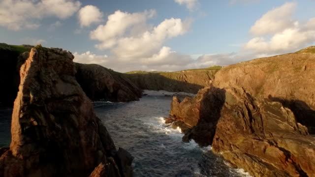 stunning aerial shot on the isle of harris, scotland, flying along the coastline at uig with sea stacks - äußere hebriden stock-videos und b-roll-filmmaterial