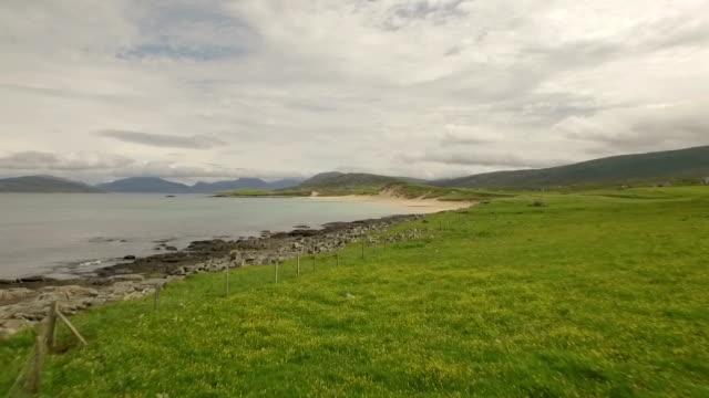 stunning aerial shot on the isle of harris, scotland near the coast showing water and beaches - äußere hebriden stock-videos und b-roll-filmmaterial