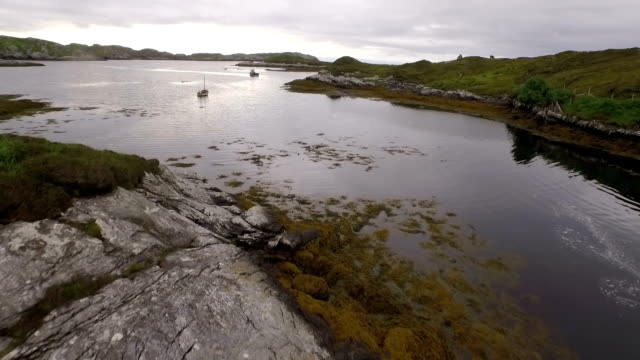 stunning aerial shot on the isle of harris, scotland near the coast flying over a small fishing boat - äußere hebriden stock-videos und b-roll-filmmaterial