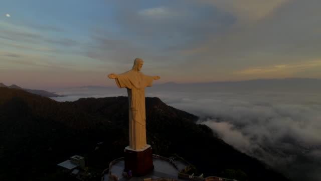 vidéos et rushes de stunning aerial view of christ the redeemer at sunrise in rio de janeiro brazil - corcovado