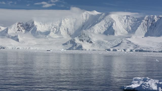 stunning and pristine glacial and mountain scenery in the gerlache strait separating the palmer archipelago from the antarctic peninsular off anvers island. the antartic peninsular is one of the fastest warming areas of the planet. - shelf stock videos & royalty-free footage