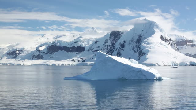 stunning and pristine glacial and mountain scenery in the gerlache strait separating the palmer archipelago from the antarctic peninsular off anvers island. the antartic peninsular is one of the fastest warming areas of the planet. - antarctica iceberg stock videos & royalty-free footage