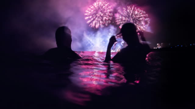 vídeos de stock, filmes e b-roll de stunning animated picture with cinemagraph effect of a girls contemplating the colorful fireworks at night from water in the beach during summer festivities in the mediterranean sea. - estupefação