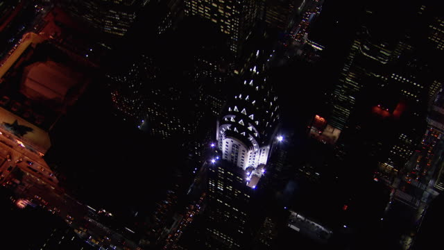 stunning birds eye view of the chrysler building, one of new york city's famous skyscrapers, at night. - chrysler building stock videos & royalty-free footage