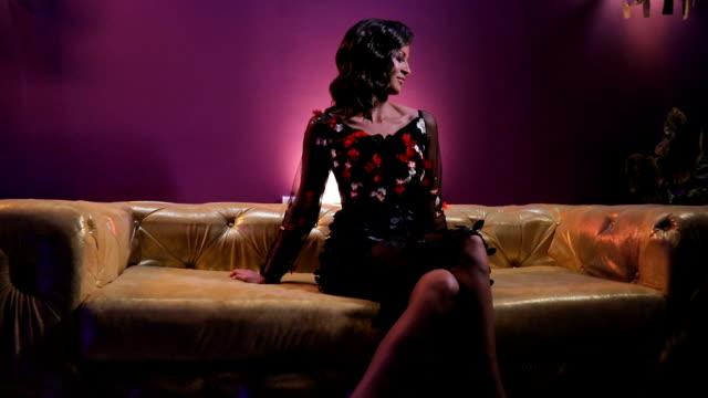 vídeos de stock, filmes e b-roll de impressionante senhora morena sentada no sofá colorido ouro - de pernas cruzadas