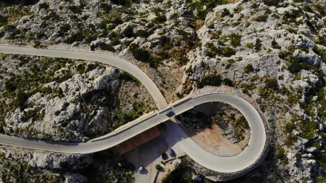 vídeos de stock, filmes e b-roll de stunning drone view of helicoid curve with eight shape in mountain road in the mountains of mallorca island. - número 8