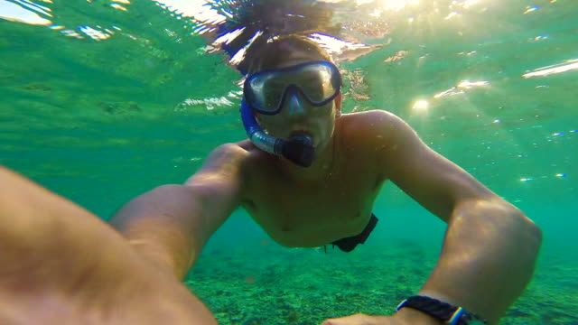 Stunning footage of guy swimming underwater in the paradise Gili islands with clear waters recorded using video selfie of action cam during travel vacations in Indonesia.