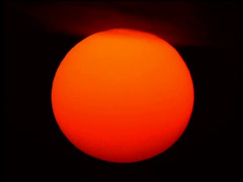 stunning huge orange sun rises slowly filling night sky, dark clouds scatter across top of sphere - orange colour stock videos & royalty-free footage