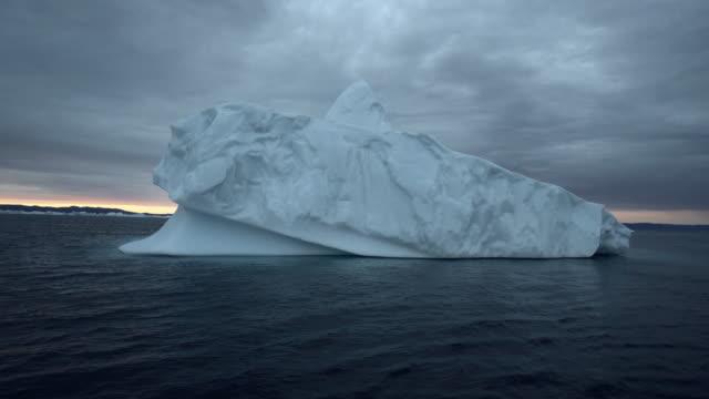 vídeos de stock, filmes e b-roll de stunning iceberg juts out of jet black choppy water at sunset in disko bay - melting