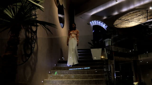 stunning lady in white dress walking down the steps - white dress stock videos & royalty-free footage