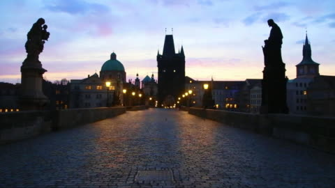 vídeos y material grabado en eventos de stock de stunning motion clip walking in the charles bridge of prague with the city landmarks and beautiful sunrise sky during morning day without people. - praga