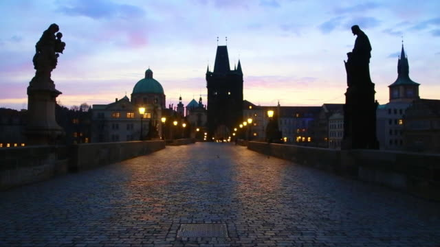 vidéos et rushes de stunning motion clip walking in the charles bridge of prague with the city landmarks and beautiful sunrise sky during morning day without people. - culture tchèque
