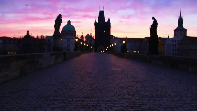 stunning motion clip walking in the charles bridge of prague with the city landmarks and beautiful sunrise sky during morning day without people. - charles bridge stock videos & royalty-free footage