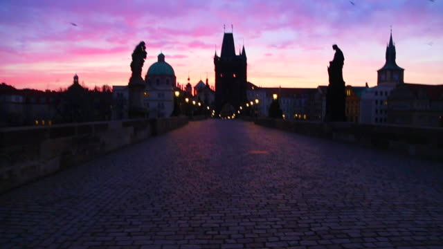 stunning motion clip walking in the charles bridge of prague with the city landmarks and beautiful sunrise sky during morning day without people. - old town bridge tower stock videos and b-roll footage