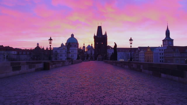 stunning motion clip walking in the charles bridge of prague with the city landmarks and beautiful sunrise sky during morning day without people. - kopfsteinpflaster stock-videos und b-roll-filmmaterial