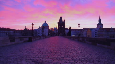 stunning motion clip walking in the charles bridge of prague with the city landmarks and beautiful sunrise sky during morning day without people. - eastern european culture stock videos & royalty-free footage