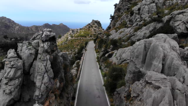 stunning mountain road between the rocky terrain in the mountains of mallorca island. - mountain road stock videos & royalty-free footage