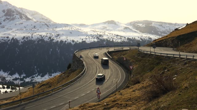 vídeos de stock e filmes b-roll de stunning mountain road pass in the pyrenees with curve and snowy summits. - fugir da realidade
