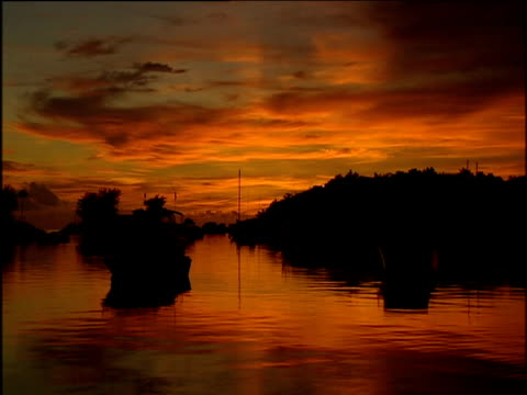 stunning pink sunset illuminates cloud which reflects from surface of water in marina small boats scattered tree line in background all silhouetted; bermuda - alberato video stock e b–roll