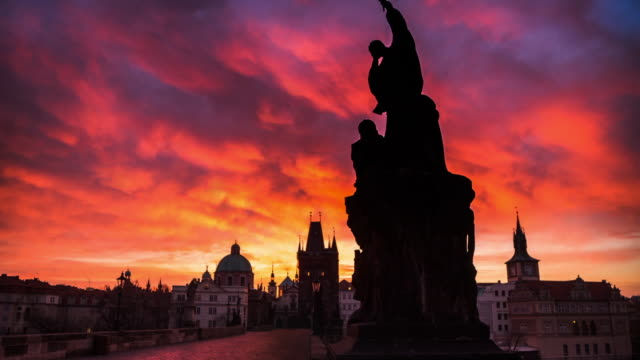 Stunning time lapse of the city of Prague taken from the famous Charles bridge during sunrise moment with burning colors in the sky during travel vacations.