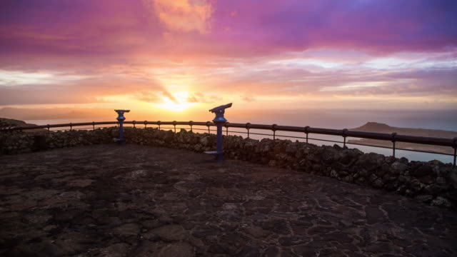 stunning time lapse of the clouds in motion during sunset in the lanzarote island from viewpoint with beautiful colors during travel vacations in the islands. cinemagraph effect. - binoculars stock videos & royalty-free footage