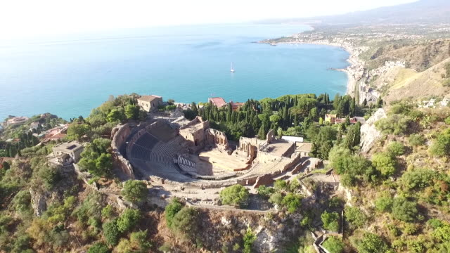a stunning view of ancient theatre of taormina by the sea in sicily, italy - ancient greece stock videos & royalty-free footage