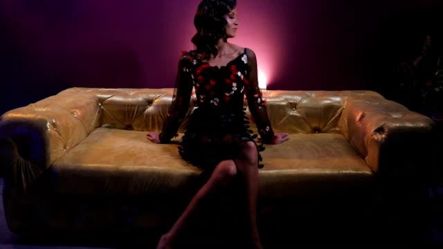 vídeos de stock, filmes e b-roll de deslumbrante mulher sentada no sofá colorido ouro - de pernas cruzadas