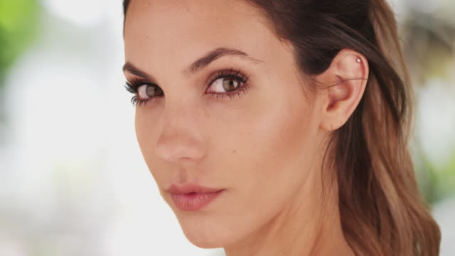 stunning young brunette staring intimately at camera on bright serene background - eyelash stock videos & royalty-free footage