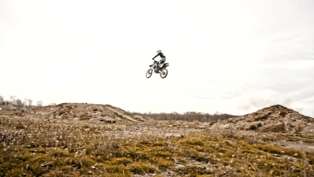 SLO MO Stunt biker jumping over dirt ramp