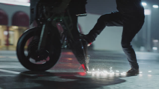 slo mo. stunt biker lands an extreme wheelie and skates on back of bike as sparks fly in rainy parking lot at night. - sportschutzhelm stock-videos und b-roll-filmmaterial
