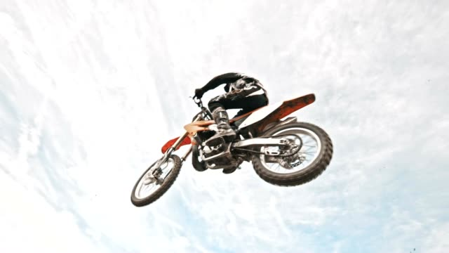 SLO MO Stunt dirt biker jumping over the camera