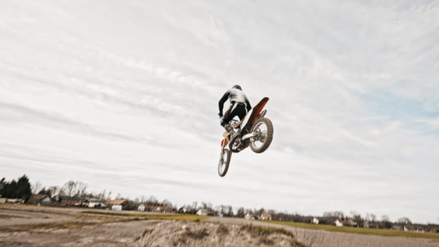 Stunt dirt biker jumping over the camera