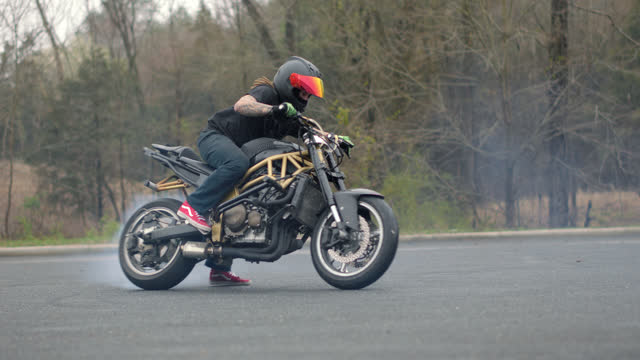 stunt motorcycle rider spins in circles burning rubber with white smoke filling the air on an empty street - tire vehicle part stock videos & royalty-free footage