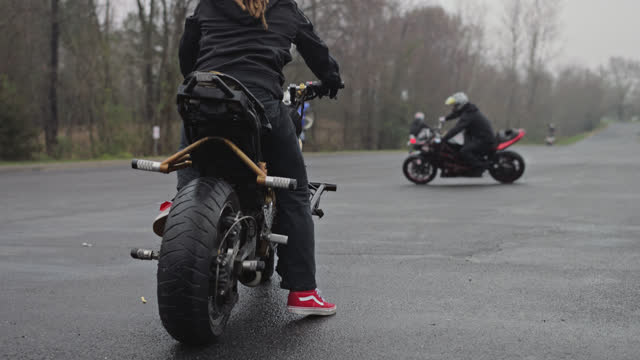vídeos de stock e filmes b-roll de slo mo. stunt motorcycle rider with brown dreadlocks rests on his gold motorcycle watching other stunt riders do tricks in an empty parking lot - gangue