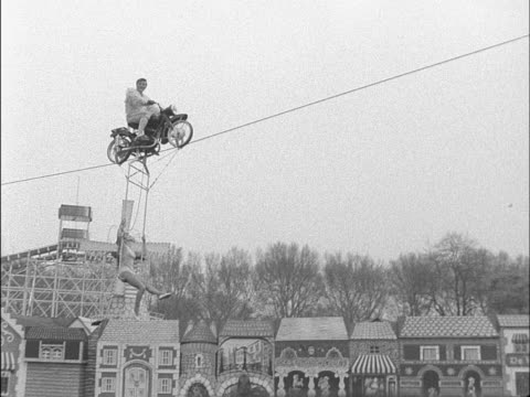 a stunt motorcyclist and his assistant perform a stunt at battersea funfair - akrobat stock-videos und b-roll-filmmaterial