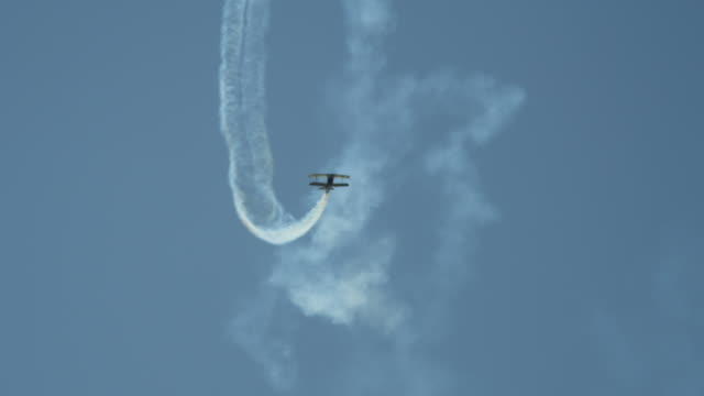 stunt plane flying loops and diving, trailing smoke - airshow stock videos & royalty-free footage