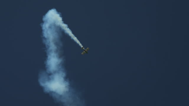 Stunt plane flying loops and rolls, trailing smoke