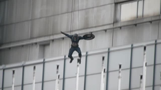 a stuntman dressed as captain america jumps off a building while filming captain america civil war on august 12 2015 in berlin germany - エディトリアル点の映像素材/bロール