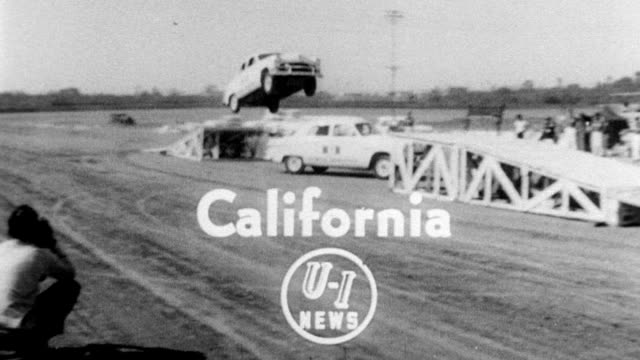 vídeos de stock, filmes e b-roll de stuntman drives car up a ramp into the air across a gap and down another ramp as a different car drives through the gap hollywood stuntmen display... - 1951