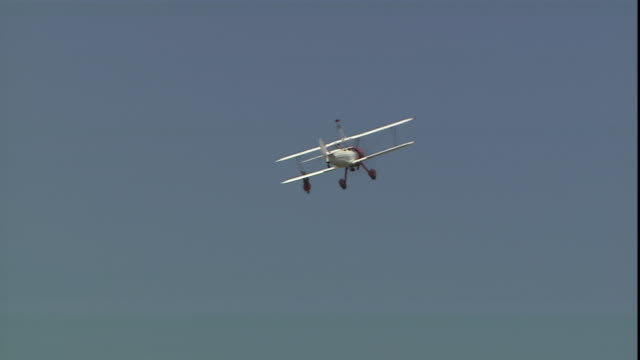 a stuntperson hangs upside down from a propeller biplane. - biplane stock videos & royalty-free footage
