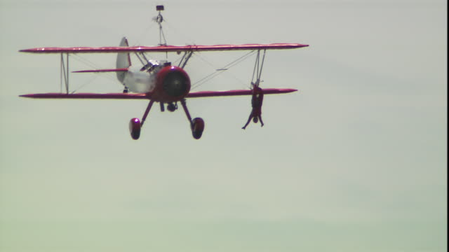 a stuntwoman hangs from a biplane as it rolls in the air. - stunt person stock videos & royalty-free footage