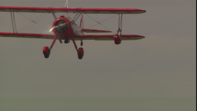 stuntwoman jane wicker hangs upside down from the wing of a flying biplane. - acrobatica aerea video stock e b–roll