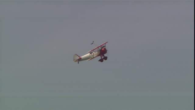 stuntwoman, jane wicker, is barely visible as she stands on the wings of a flying biplane. - stunt person stock videos & royalty-free footage