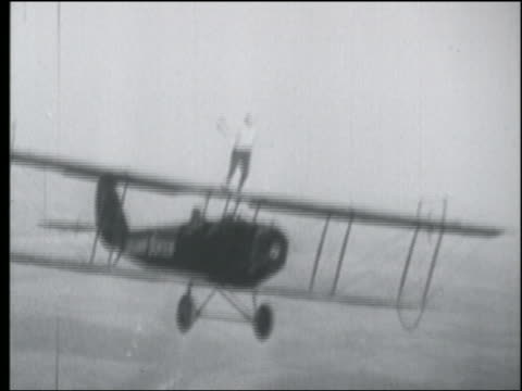 B/W AERIAL stuntwoman Lillian Boyer standing atop biplane in air + waving at camera