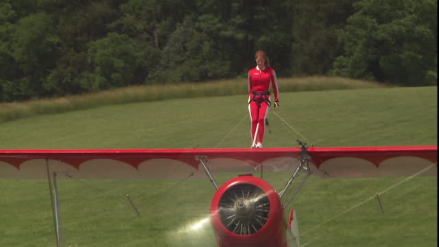 a stuntwoman waves from atop a bi-plane. - stunt person stock videos & royalty-free footage
