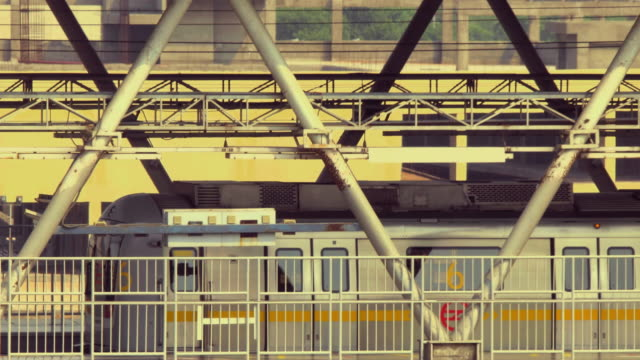A stylised shot of Delhi Metro train stopping at a metro station and passengers disembarking