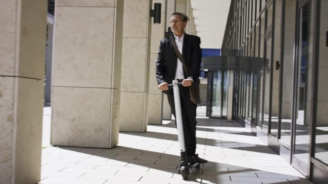stylish and active senior business man in his 60s in black suit and white shirt is riding his trendy white s-scooter. - successo video stock e b–roll