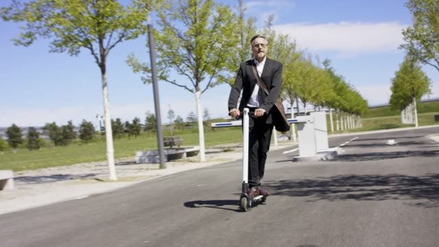 vídeos y material grabado en eventos de stock de stylish and active senior business man in his 60s in black suit and white shirt is riding his trendy white e-scooter. - descanso para comer